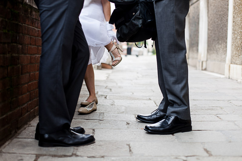 bride takes off her shoes during wedding photo service in Venice