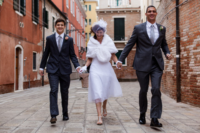 bride, bridegroom and son walking along an alley in Venice during a vow renewal photo shooting