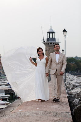 bride and groom walking along Garda Lake while posing for honeymoon photographer