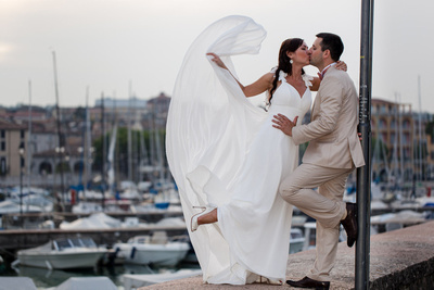 bride and groom playing with veil during honeymoon photo session at Garda Lake