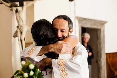 bride hugging priest during wedding photo shooting in Northern Italy