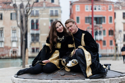 couples in Carnival outfit sitting on a well during a photo walk in Venice