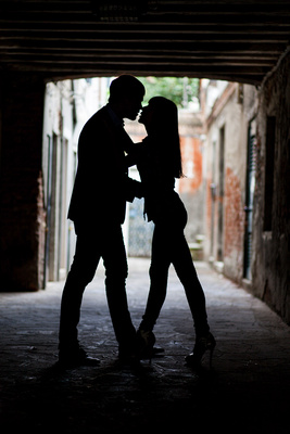 Russian couple kiss under an arcade during a honeymoon photo service in Venice