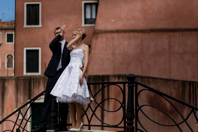 Russian couple throwing padlock keys in the channel during a wedding photo service in Venice