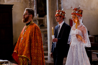 Russian couple wearing crowns and holding candles during an Orthodox wedding photo service