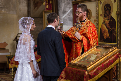 Russian couple kissing icon during an Orthodox wedding photo service in Venice