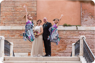bridesmaid jumpoing and couple hugging in vows renewal photo service in Venice