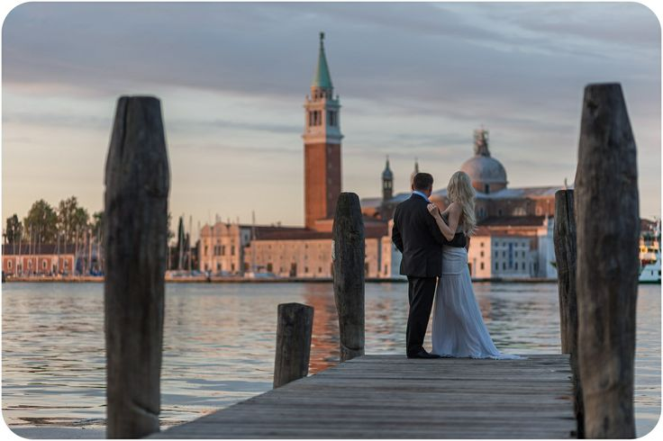 couple hugging in fromt of lagoon during couple portrait in Venice