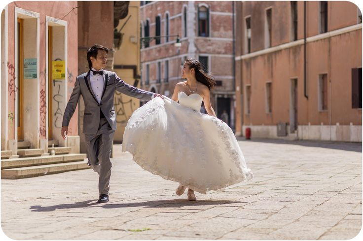 couple running during pre-wedding photo session in Venice