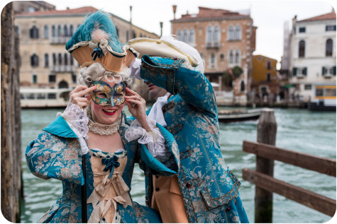 couple getting dressed in fancy Carnival dresses during photo walk in venice