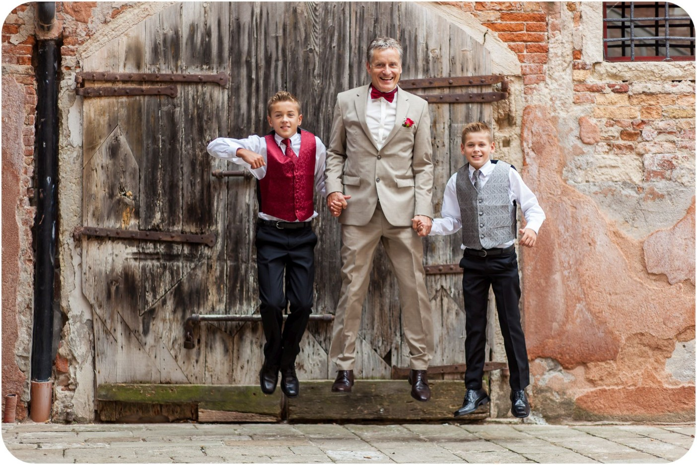 groom jump with children during wedding photo session in Venice