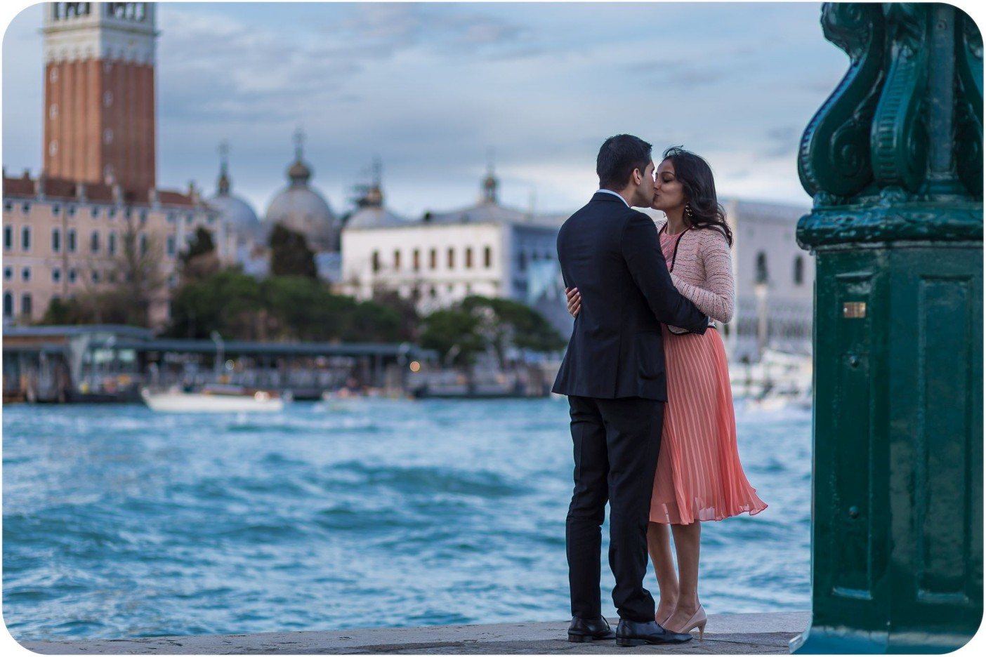 couple kiss in front of lagoon during engagement photo session in Venice