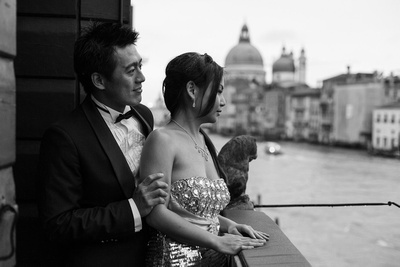 couple standing on a terrace facing the Canal Grande during a photo shooting in Venice