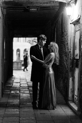 Canadian couple hugging under an arcade during honeymoon photo service in Venice