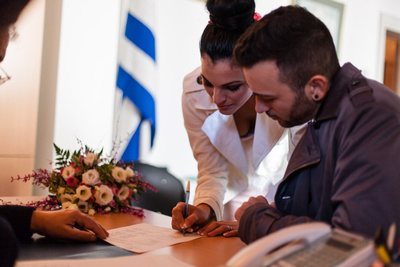 bride and groom signing documents during elopment photo service in Venice.