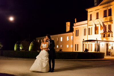 bride and groom kissing in front of ancient villa during wedding photo reportage in Veneto