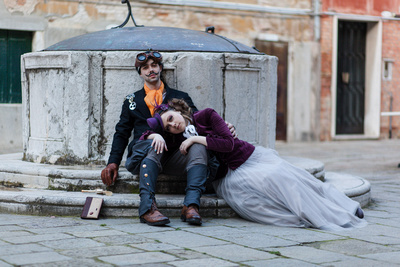 couple sitting on a well in Venice during steampunk photo reportage