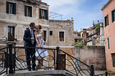 couple standing on a iron bridge during a wedding photo service in Venice
