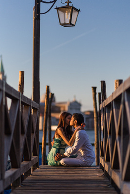 Asian couple kissing in front of the lagoon in pre-wedding photo shooting in Venice