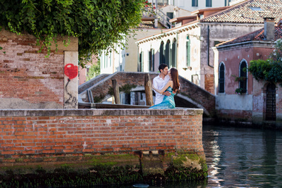 Asian couple kissing during photo walking tour in Venice