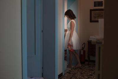 bride entering hotel room after wedding photo reportage in Venice