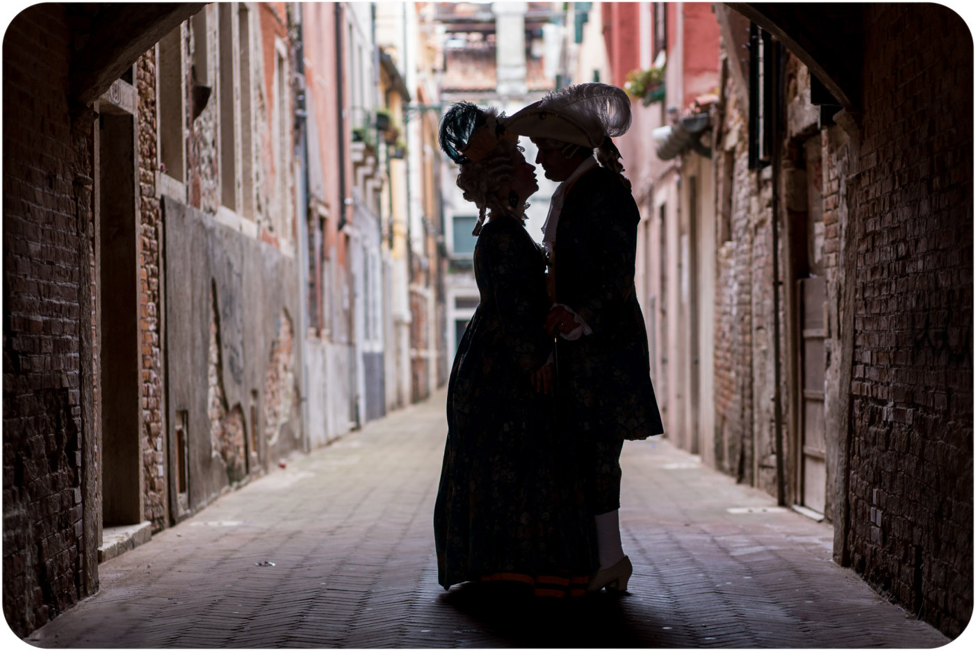 couple kiss under arcade during Carnival photo service in Venicece
